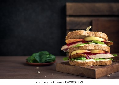 Turkey or Chicken leftover sandwich with stuffing and cranberry sauce. Freshly made from Thanksgiving or Christmas turkey leftovers on crusty wholemeal bread.