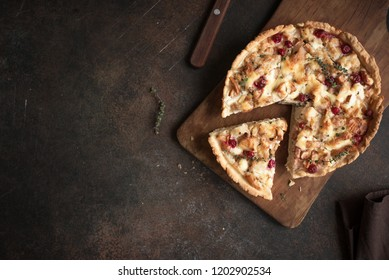 Turkey or Chicken leftover Tart Pie with pears, cheese and cranberries. Thanksgiving or Christmas turkey leftovers homemade quiche, copy space, top view.