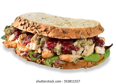 Turkey, chicken sandwich with stuffing and cranberry sauce. Freshly made from Christmas leftovers on crusty whole grain bread. Isolated on white with small drop shadow.