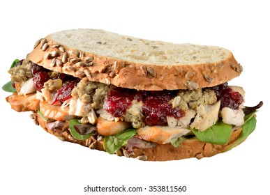 Turkey, chicken sandwich with stuffing and cranberry sauce. Freshly made from Thanksgiving, Christmas leftovers on crusty whole grain bread. Isolated on white.