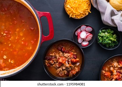 Turkey chili garnished with fresh radishes, green onions and cheddar cheese