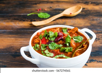 Turkey Chili. Stewed with black and white beans, tomatoes, bell pepper, onion, garlic, thyme, cinnamon, chocolate and fresh cilantro. Soup bowl on wooden table.