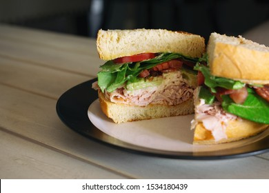 Turkey club sandwich with avocado, bacon and tomato on fresh bread cut in half.