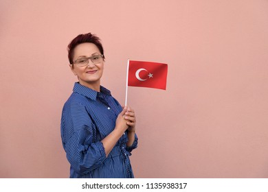 Turkey flag. Woman holding Turkish flag. Nice portrait of middle aged lady 40 50 years old with a national flag of Turkey over pink wall background.