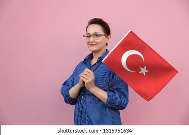 Turkey flag. Woman holding Turkish flag. Nice portrait of middle aged lady 40 50 years old holding a large flag over pink wall background on the street outdoors.