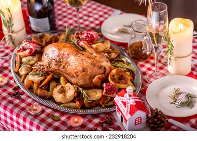 Turkey garnished with potato, apples and garnet on Christmas decorated table