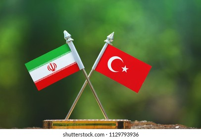 Turkey and Iran small flag with blur green background