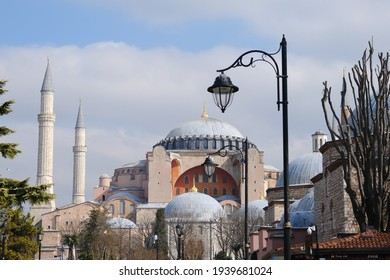 Turkey istanbul 03.03.2021. Facade and outside of Hagia sophia (aya sofya) mosque and minarets from sultanahmet square with many tourists, palm trees during overcast sky background during day time.