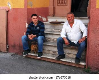 TURKEY, IZMIR - April 28, 2013: Two men sitting on the steps of the house on Namazgah Mahallesi