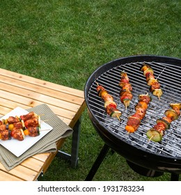 Turkey kebab on brazier, picnic. Barbeque, bbq meat. Green grass background. Delicious summer food. Copy space.