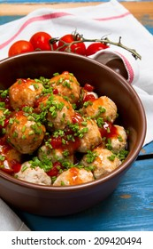 Turkey meatballs with tomato sauce and chives onion in a ceramic pan
