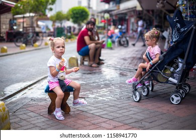 In Turkey on the markets two sisters twin, waiting in the street, one in a pushchair and the other on a Turkish stool