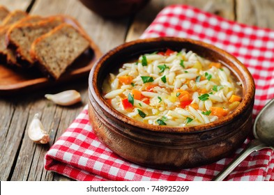 Turkey orzo vegetables soup on a wood background. toning. selective focus