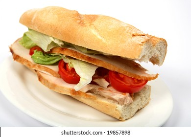 A turkey salad sandwich on a plate with a white background.