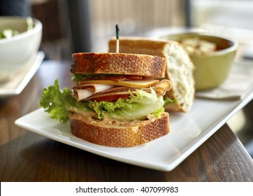 Turkey sandwich with bacon, cheese, lettuce tomato and mayonaise on wheat bread with soup