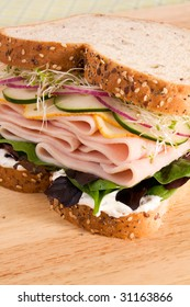 Turkey sandwich with muenster cheese, cucumbers, red onion, alfalfa, lettuce, and an herb cream cheese spread.