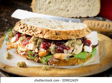 Turkey sandwich with stuffing and cranberry sauce. Freshly made from Thanksgiving or Christmas turkey leftovers on crusty wholemeal bread.