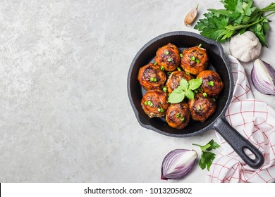 Turkey spinach cheese meatballs in cast iron skillet on white stone background. Top view, copy space.