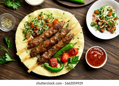 Turkish Adana Kebab with fresh vegetables on flatbread over wooden background. Top view, flat lay