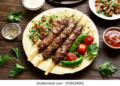 Turkish Adana Kebab with fresh vegetables on flatbread over wooden table. Tasty food in arabic style. Close up view