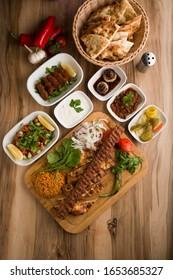 Turkish adana kebap with garnitures on wooden plate