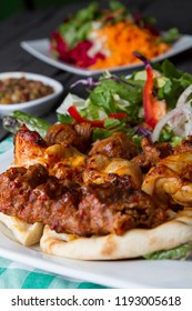 Turkish and Arabic Traditional Adana, Lamb and Chicken Kebab serving with salad, yogurt, onion, pepper, bulgur and parsley on rustic black wood table. Dark photography concept with copy space.