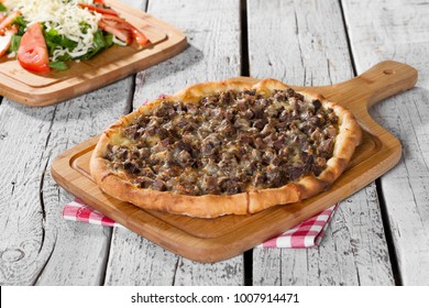 Turkish and Arabic Traditional Baked Ramadan Food Pide or Pizza ingredients with sliced halal lamb meat , butter, cheese and spicy herbs on rustic white wooden background. Copy space for text area.
