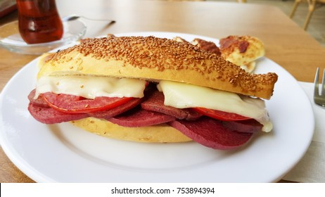Turkish and Arabic Traditional Breakfast Sandwich ingredients with ham, cheese and sliced tomato serving on wood table hot tea background. Kumru