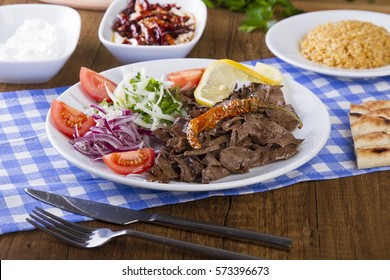 Turkish and Arabic Traditional Liver Doner Kebab serving witt salad, yogurt, lettuce, pita bread, onion, tomato and rice pilav in white plate on garnish restaurant background