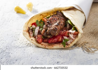 Turkish and Arabic Traditional Ramadan Adana Kebab Roll Wrap serving with yogurt, aubergine salad and hot pepper pickles on rustic wooden background.