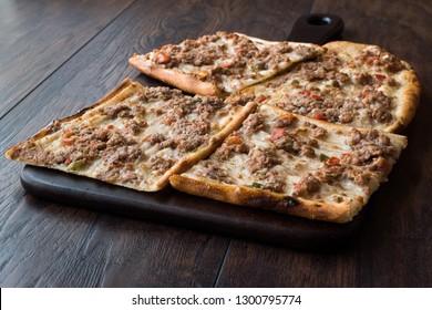 Turkish and Arabic Traditional Ramadan Bread Sliced Etli Ekmek Kebab with Minced Meat (Pide or Lahmacun Kebap) serving on wood