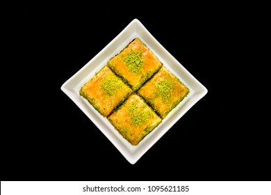 Turkish and Arabic traditional Ramadan dessert - baklava with pistachios on white plate. Isolated on black background.