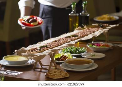 Turkish and Arabic traditional ramadan dinner food pide ( etli ekmek ) on iftar table with lentil soup, cig kofte, salad, parsley and tomato soup. Waiter serving icli kofte and fried potato.