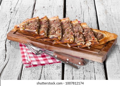 Turkish and Arabic Traditional Ramadan Food Pide on bamboo cutting board serving with salad, knife, fork and napkin on wood white background. Thin piece of dough topped with minced meat and herbs.
