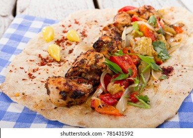 Turkish and Arabic Traditional Ramadan Grilled Chicken Kebab Roll Wrap serving with parsley, aubergine salad, onion and hot pepper pickles on rustic wooden background.