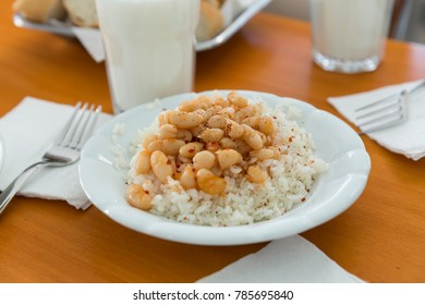 Turkish and Arabic Traditional Ramadan hot bean stew with a tasty tomato sauce, ayran, sliced bread and rice turkish pilav in white plate on wood table background.