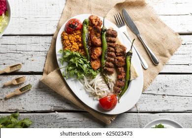 Turkish and Arabic Traditional Ramadan Mix Kebab Plate inside Adana, Urfa, Chicken, Lamb, Liver and Beef on lavash bread with salad.