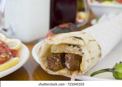 turkish and arabic traditional ramadan shish kebab roll wrap serving with yogurt aubergine salad
