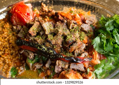 Turkish and Arabic Traditional Ramadan Sliced Lamb Meat Kebab with pide bread, salad and bulgur rice on white rustic wood background.
