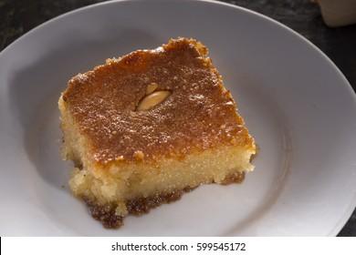 Turkish and Arabic Traditional Sweet pie Basbousa, Revani (Namoora) with almond cardamom coconut semolina selective focus on black rustic background