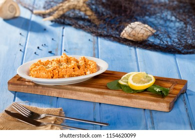 Turkish and Arabic Traditional Tomato Paste ingredients with carrot, curd cheese, walnut, thyme and pumpkin serving on bamboo cutting board serving with fishing net, shell, knife, fork and napkin.