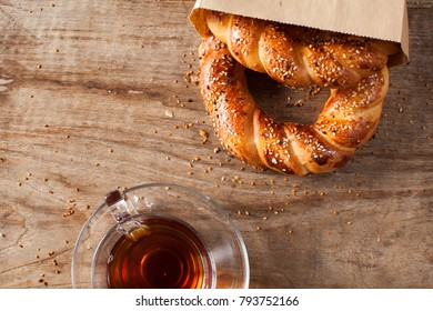 Turkish bagel Simit in paper bag with traditional tea glasses on wood table