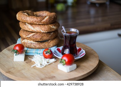 Turkish Bagel Simit, tea, cherry tomato and cheese on a blue plaid napkin on a wooden surface.