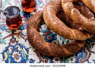 Turkish Bagel Simit with tea on ottoman pattern surface.