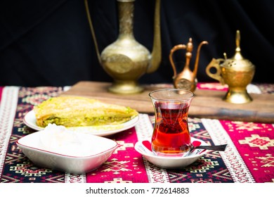 Turkish baklawa with ice cream and pistachios and tea in pear shaped glass. Oriental style arrangement with vintage jars on ethnic table cloth, copy space still life
