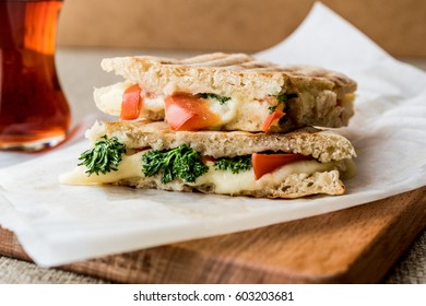 Turkish Bazlama Tost / Toast sandwich with melted cheese, tomatoes, dill and tea.
