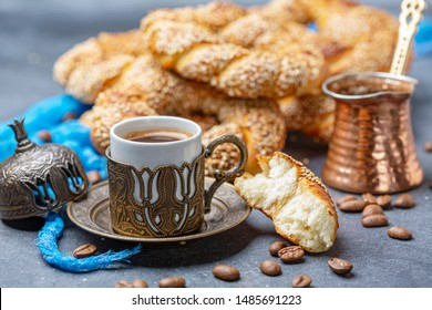 Turkish black coffee served in traditional ceramic cup with sesame bagel, selective focus.