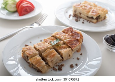 Turkish borek on breakfast table, rolled and flat, called kol and su respectively, with olives and tomatoes