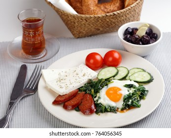 Turkish breakfast with fried egg, sucuk, cheese, vegetables, simit, and tea