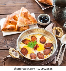 Turkish breakfast  - fried eggs with sausages (sucuk) and spices in a pan on a wooden background.